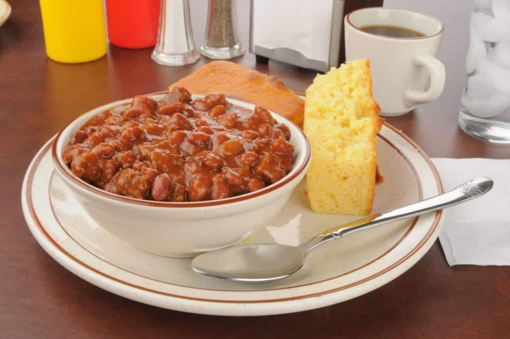 Bowl full of beans with cornbread on a plate