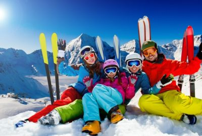 Family sitting in snow while skiing in mountains