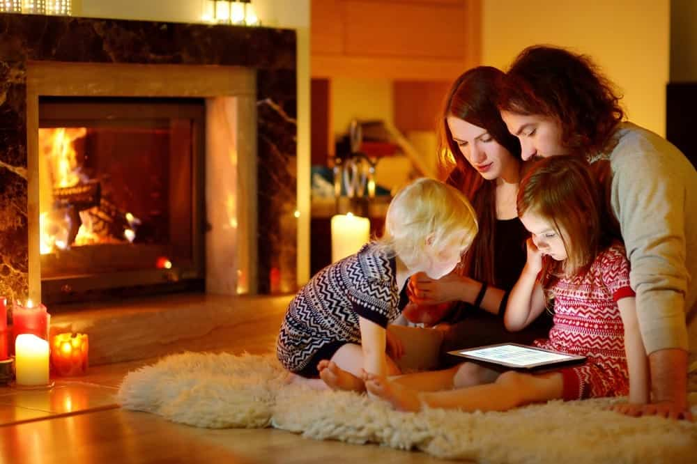 young family look at tablet in front of fireplace at Smoky Mountain cabin