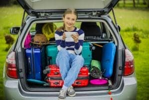 Young girl sitting on suitcases in the back of a trunk.