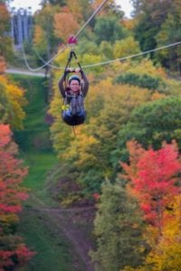 A woman riding on a zipline in the fall.