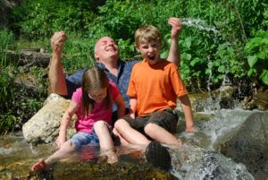 Father and kids playing in river in Smoky Mountains